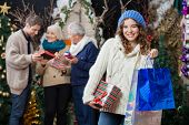 Portrait of beautiful young woman holding Christmas presents and shopping bags with family standing