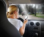 image of unsafe  - A young woman is on the cell phone texting and driving with a road in the windshield for an danger or distracted driving concept - JPG
