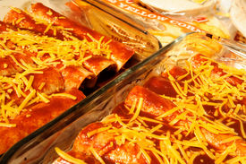 stock photo of pasilla chili  - Homemade enchiladas ready to go in the oven made with cheddar cheese corn tortillas and pasilla chili enchilada sauce - JPG