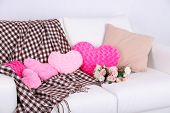 Pink heart shaped pillows on white sofa