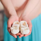 Pregnant belly with newborn knitted baby booties, soft focus.
