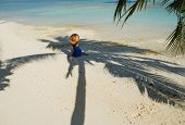 Woman in blue dress on a tropical beach at Maldives sitting in palm tree shadow