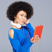 Beautiful African American woman with her music standing with the earphones around her neck listenin