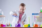 stock photo of naturalist  - Inquisitive naturalist mixes reagents in flask - JPG