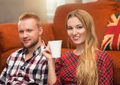 Couple Relax At Home With Cup Of Coffee In The Living Room