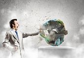 Young determined businessman crashing Earth planet with punch. Elements of this image are furnished