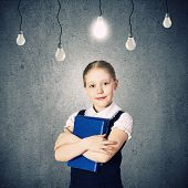Cute school girl against grey wall with bulbs hanging above