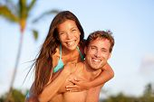 stock photo of piggyback ride  - Vacation couple fun on beach - JPG