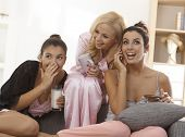 stock photo of pyjama  - Three girls in pyjamas at home listening as one talking to boyfriend - JPG
