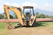 stock photo of hoe  - Back hoe parked on green grass at a construction site - JPG