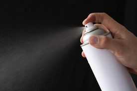 image of ozone layer  - White spray can spraying in action with hand on black background - JPG