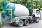 pic of cabs  - Concrete mixer truck with green cab over trees - JPG