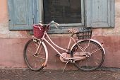 stock photo of nostalgic  - aged nostalgic pink bicycle leaning against house wall and window - JPG