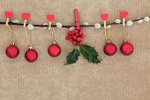 picture of pussy-willows  - Christmas red bauble decorations with holly hanging on a pussy willow branch over old brown paper background - JPG