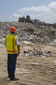 picture of landfills  - Worker watching digger moving waste at landfill site - JPG