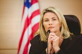 image of court room  - Portrait of a serious judge with american flag behind her in the court room - JPG