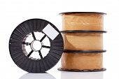foto of alloys  - Packed package welding wire copper or brass alloy spools isolated on white with an empty clear label - JPG