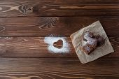 stock photo of brownie  - Chocolate brownie with powdered sugar heart close - JPG