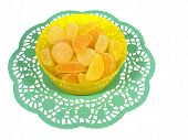 stock photo of laxatives  - Yellow sugar sweeties in a plastic  bowl on a green paper lace over white - JPG