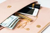 image of clutch  - Cosmetics jewelry money and smartphone in an open beige woman