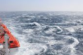 foto of hurricane wind  - Orange topped lifeboats on a large ship ploughing through rough seas in sunshine - JPG