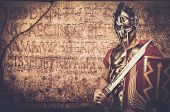 stock photo of legion  - Roman legionary soldier in front of  wall with ancient writing  - JPG