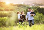 picture of young adult  - Happy young family spending time together outside in green nature - JPG