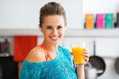 stock photo of smoothies  - Portrait of smiling fitness young woman with glass of pumpkin smoothie - JPG