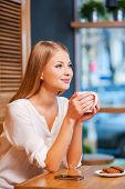 image of toothless smile  - Side view of beautiful young smiling woman enjoying coffee in cafe - JPG