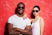 image of shot glasses  - Beautiful young mixed race couple in glasses standing against red background and smiling - JPG