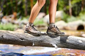 stock photo of crossed legs  - Hiking man crossing river in walking in balance on fallen tree trunk in nature landscape - JPG