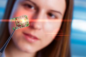 stock photo of microchips  - Girl shows new microchip on plate  that can be implanted into a paralyzed patient - JPG