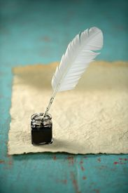 stock photo of inkwells  - Inkwell and feather with old paper on grunge table - JPG