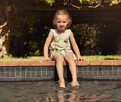 pic of wet feet  - Adorable little girl enjoying sitting by edge of pool on sunny day - JPG