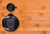 image of kettling  - Little black tea cup and a kettle on wooden background - JPG