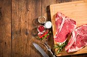 Постер, плакат: Raw fresh beef steaks and seasoning on wooden background