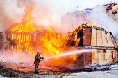 foto of firemen  - Fireman extinguishes a fire in an old wooden house - JPG