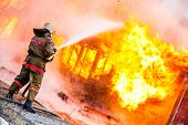 stock photo of firemen  - Fireman extinguishes a fire in an old wooden house - JPG