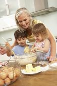 picture of grandmother  - Grandchildren Helping Grandmother To Bake Cakes In Kitchen - JPG