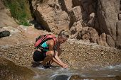 stock photo of wild adventure  - Adventure girl wash her face in the wild river - JPG
