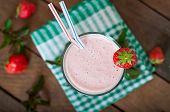 stock photo of strawberry  - Strawberry milkshake smoothie with fresh strawberry on a wooden background - JPG