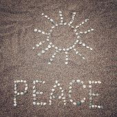 stock photo of peace  - Peace word written with pebbles on the sand  - JPG