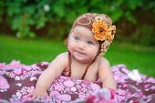 picture of knitted cap  - Cute baby crawling outdoors in brown knitted cap - JPG