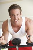foto of exercise bike  - Young Man On Exercise Bike - JPG