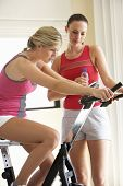 stock photo of exercise bike  - Young Woman On Exercise Bike With Trainer - JPG