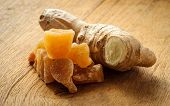 foto of home remedy  - Closeup dried candied crystallized ginger pieces and fresh root on wooden table - JPG