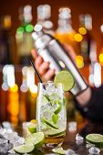 foto of mojito  - Mojito cocktail drink on bar counter with barman holding shaker on background - JPG