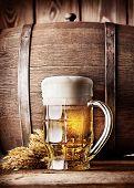 picture of beer mug  - Faceted mug of light beer on a background of the old wooden barrels - JPG