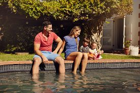 picture of hot couple  - Happy young couple sitting on the edge of swimming pool with their kids enjoying a hot summer day near pool - JPG