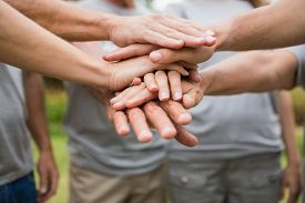 foto of moral  - Happy volunteer family putting their hands together on a sunny day - JPG